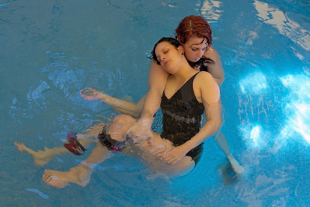 Anat Juran holding a woman in a black swimsuit by the leg as she supports her body in the water during a Watsu session