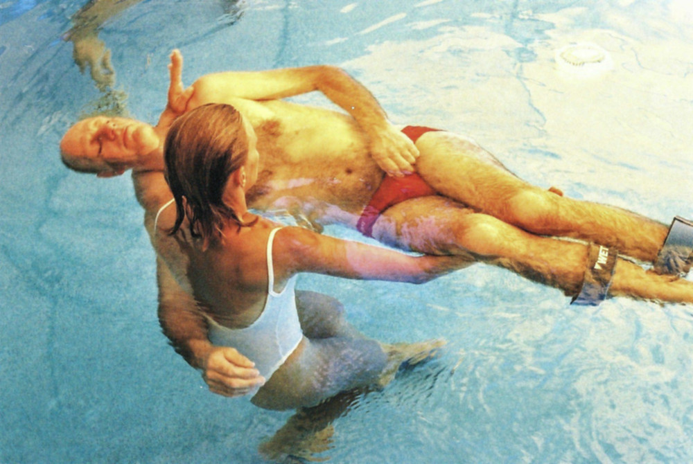 A view from above of a blond woman in a white bathing suit holding an older man wearing red swimmers closing his eyes in a pool
