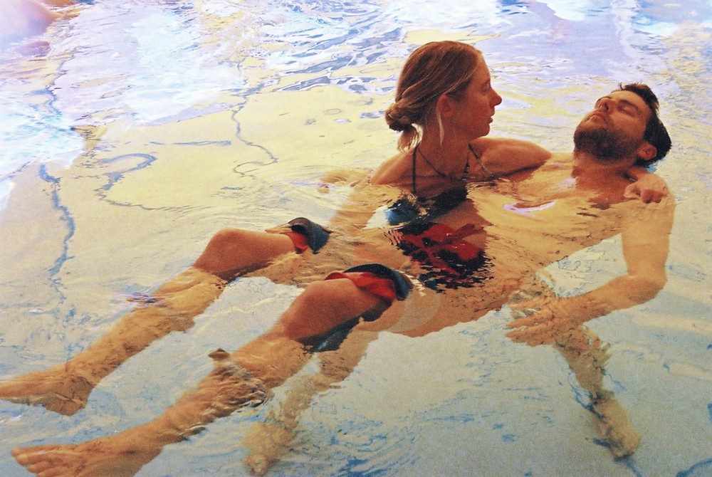 A blond women is holding a young man with dark hair in a pool with golden warm light while he closes his eyes and wears floats