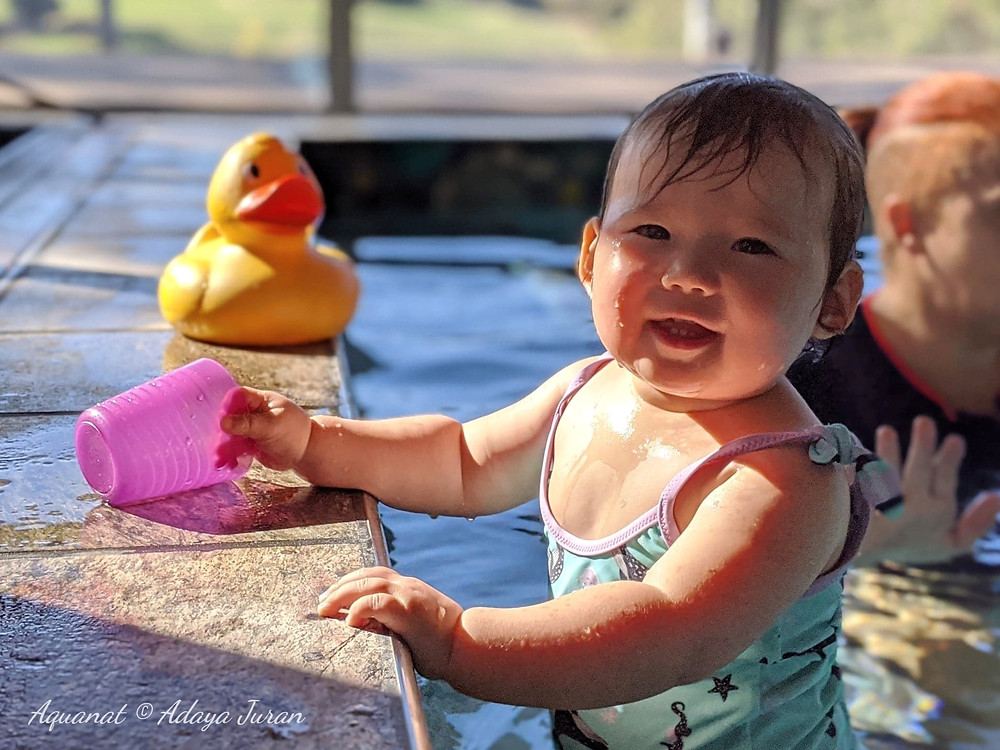 Little baby girl in light blue swimsuit is smiling having fun and playing with rubber ducky in her swimming lesson
