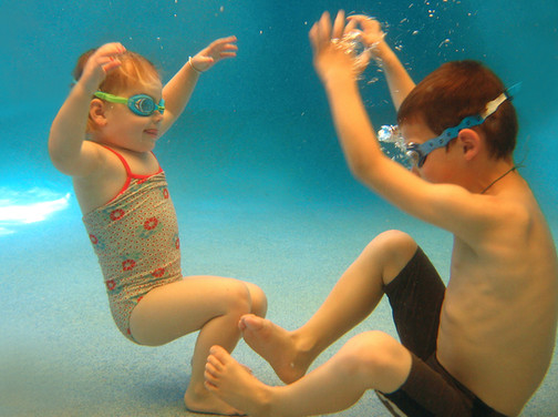 Sister and brother playing a game underwater during their swimming lesson