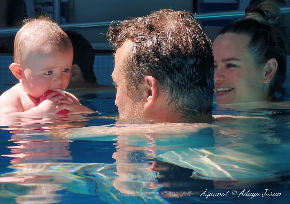 Baby holding a red toy looking into their parent's eyes during a swimming lesson