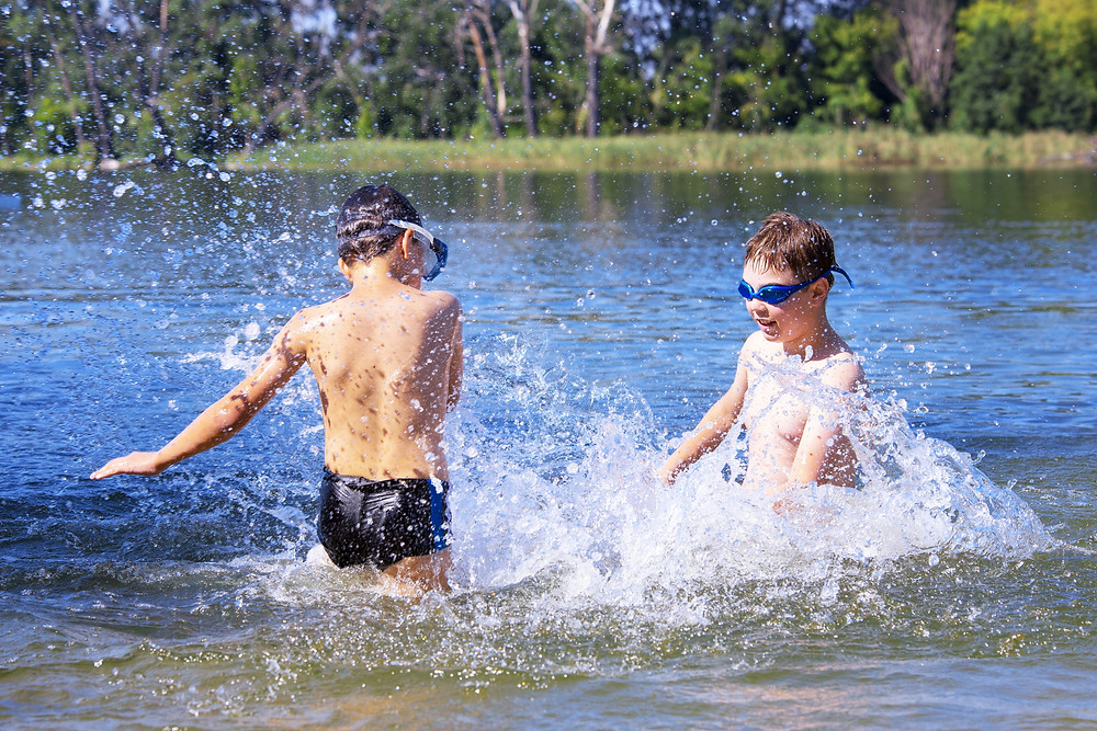View of two boys happily splashing water as they play at the water's edge