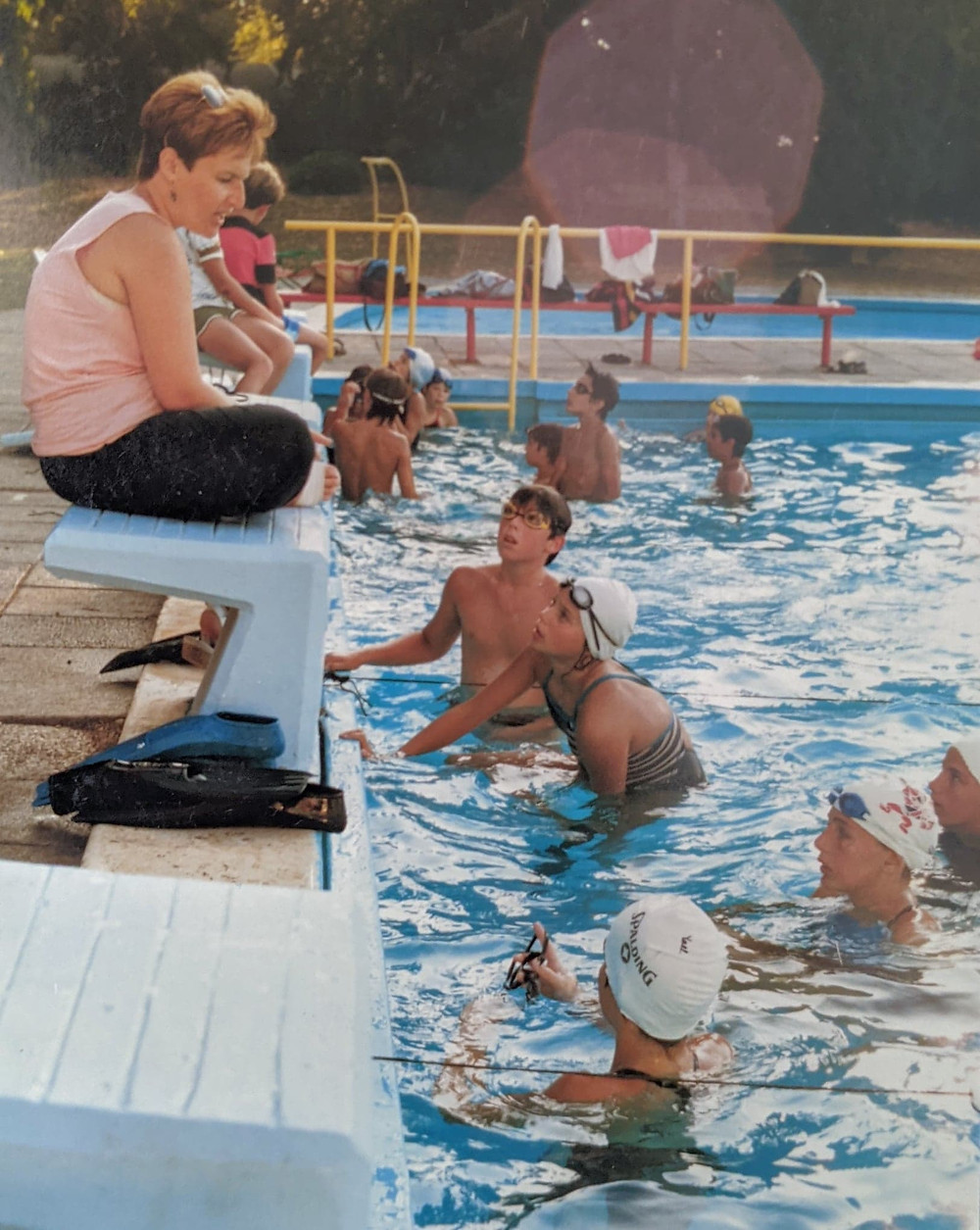 An old photo of young swim coach Anat Juran sitting out of a pool while teaching kids to swim