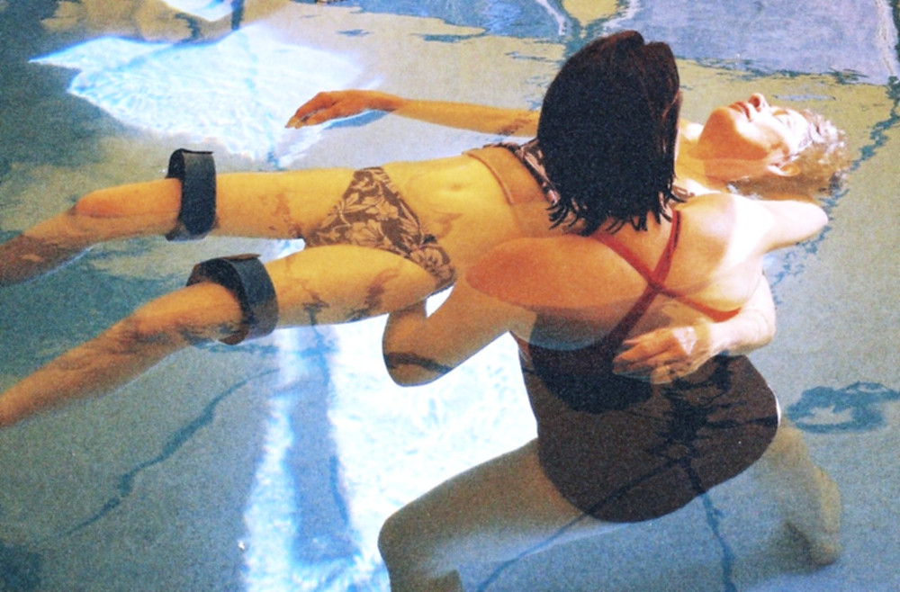Top view of woman with dark hair floating an older woman in water at a pool during a Watsu course