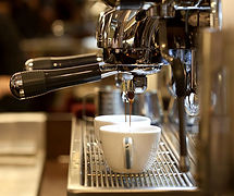 espresso machine brewing into white mugs