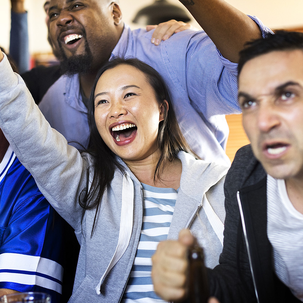 Friends cheer together at a sports bar.