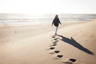 rear-view-of-senior-woman-walking-on-san