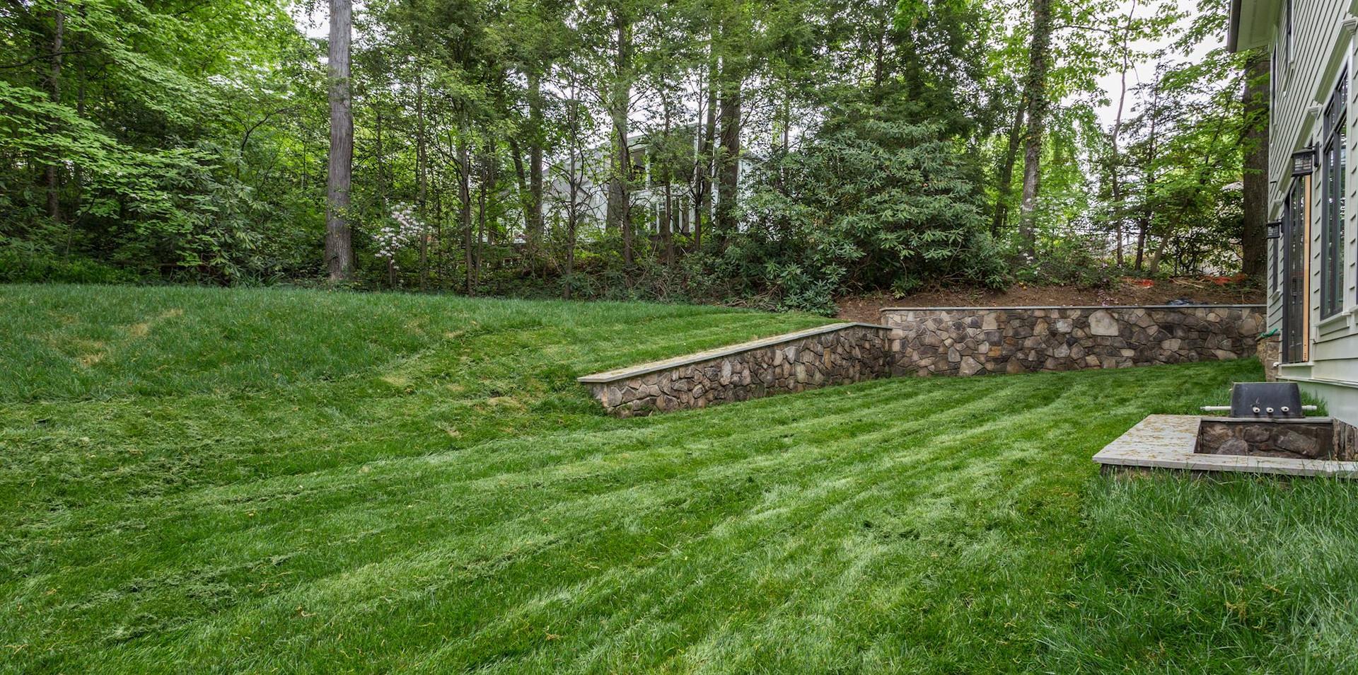 Large bi-level backyard with stone wall