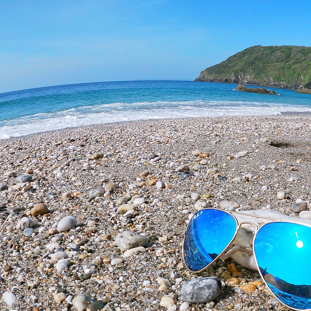 A pair of sunglasses on a beach