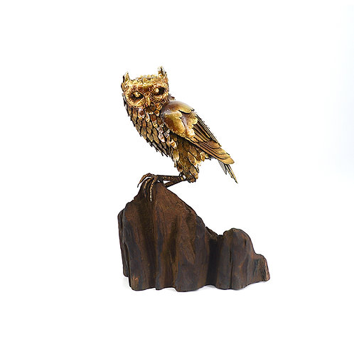 Iron owl on wood branches