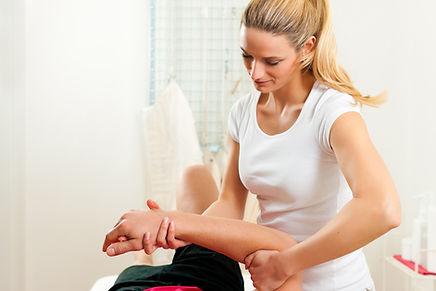 Physiotherapist treating shoulder sports injury
