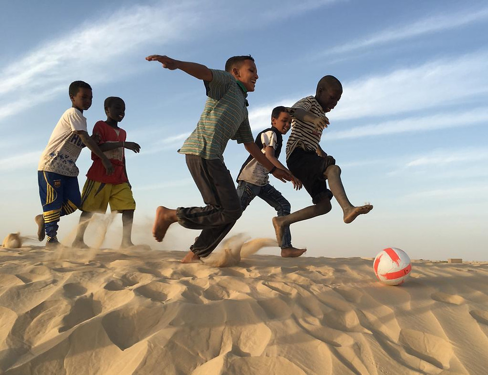 Children play with a donated soccer ball in Timbuktu.