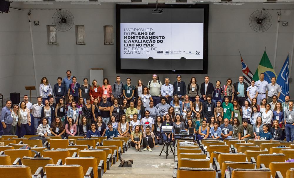 Muitas pessoas reunidas em frente a um telão escrito I Workshop do Plano de Monitoramento e Avaliação do Lixo no Mar no Estado de São Paulo, evento realizado em dezembro de 2019 no Instituto Oceanográfico da Universidade de São Paulo (USP)