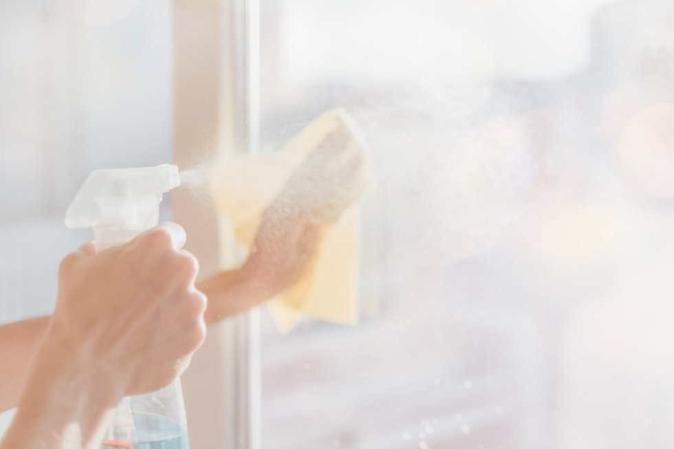 Soft-focus pastel photo of hand squeezing trigger of spray bottle while cleaning window.