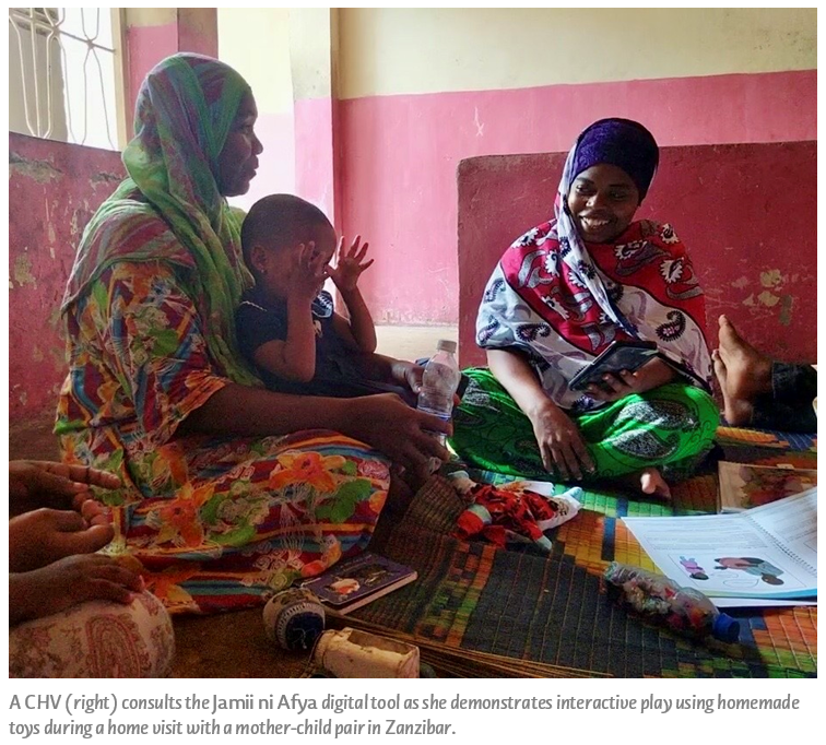 A CHV (right) consults the Jamii ni Afya digital tool as she demonstrates interactive play using homemade toys during a home visit with a mother-child pair in Zanzibar.