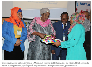 Ambassador Amina Salum Ali (center), Minister of Business and Industry, cuts the ribbon of the Community Health Strategy manual, officially launching the revised strategy—and with it, Jamii ni Afya.