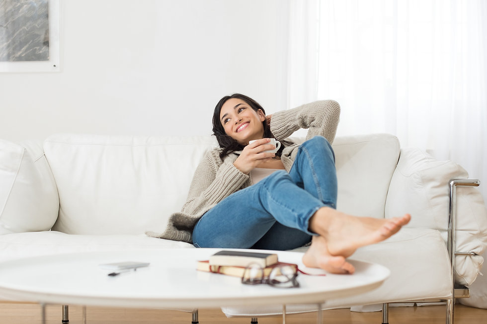 Young smiling woman sitting on sofa and