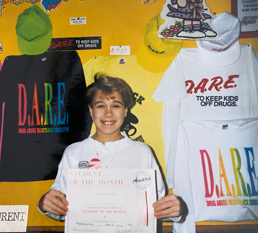 """Author as a child smiling while holding their """"Student of the Month"""" award in front of a wall with pinned up D.A.R.E clothing"""