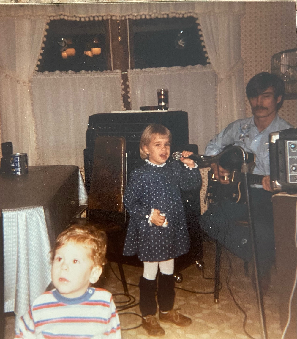 Author as child wearing a polka dotted dress holding a microphone singing, adult male playing the guitar another child looking off in the distance