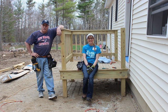 Author sitting on a newly constructed deck with a man standing next to her.