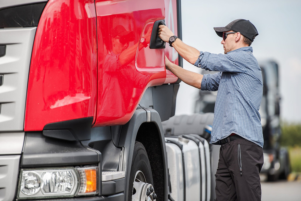Driver checking their truck due to notification from transportation management system Custella.