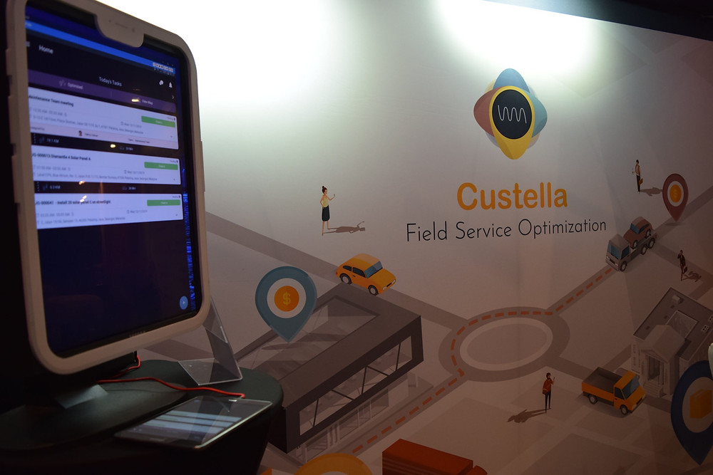 Custella software on a computer next to a wall that says Custella Field Service Optimization