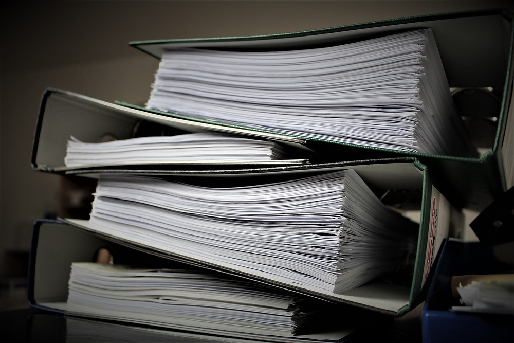 Stacks of paperwork that can be avoided with Custella, a field service management software