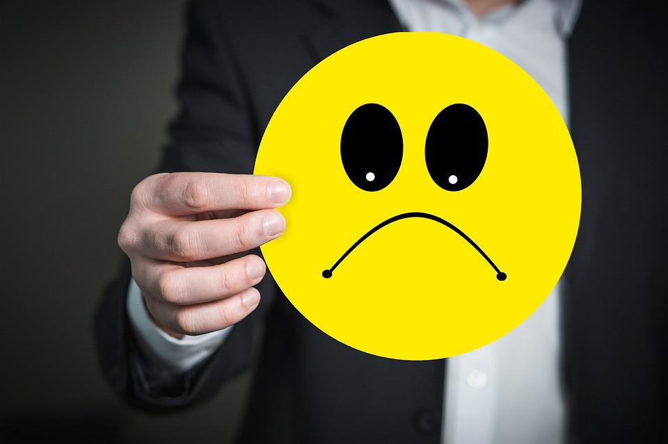 Person holding a sad face