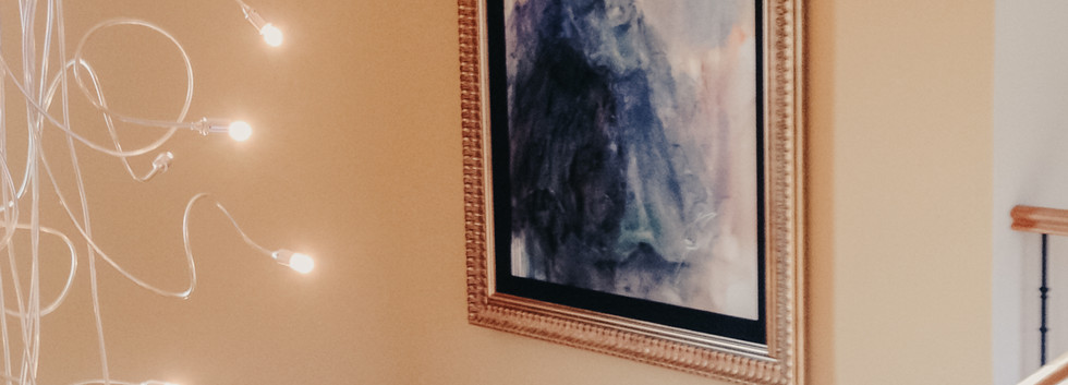 artwork painting of a lady hung on a stairwell wall with fairy lights to foreground
