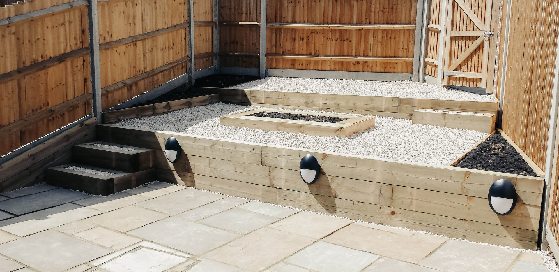 landscaped small rear garden with stepped feature, paved patio, external lights, gravel, central raised bed and wooden fence panels