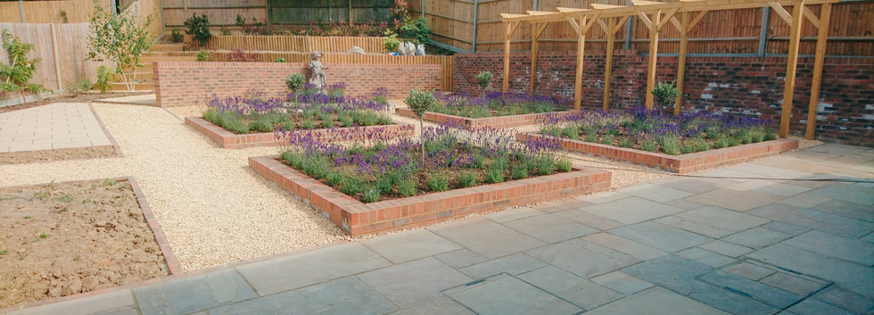 fully landscaped garden with paved patio, gravel paths, brick beds and curved wall, custom built pergola and lavender
