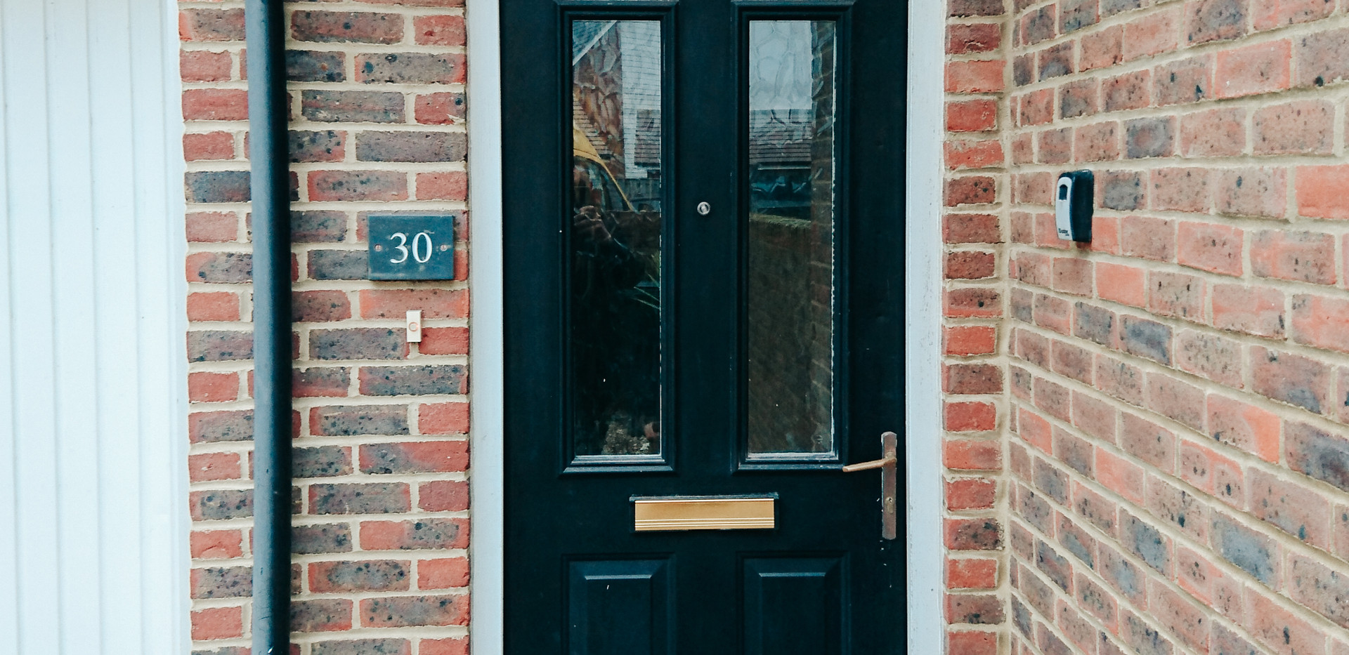 brick house with black UPVC door, canopy and external security lights
