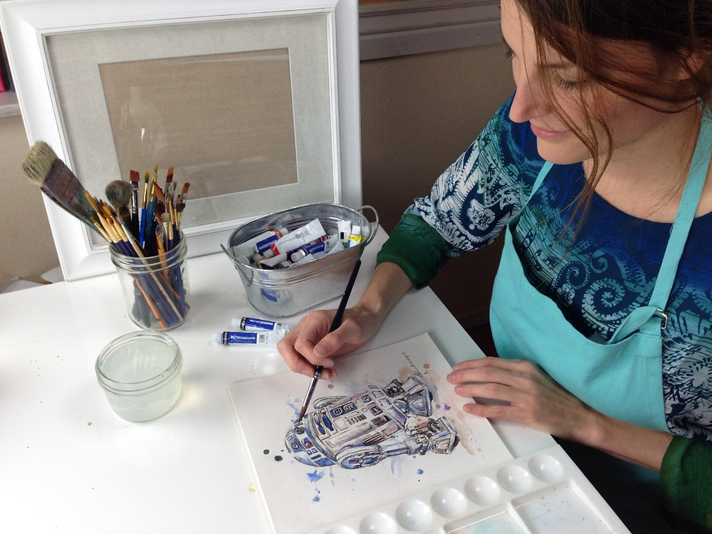 woman painting a picture with watercolors