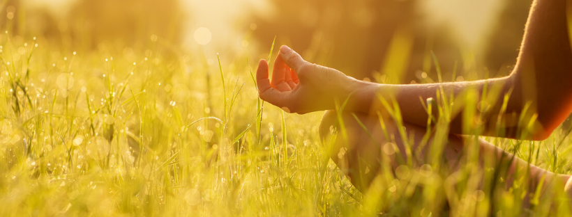 Lady's hand resting on her knee while sitting in a meditative seated yoga pose in the long grass in the sunshine