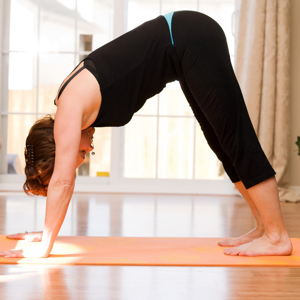 middle aged lady wearing black doing downward dog yoga pose on an orange yoga mat