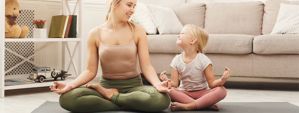 mother and young daughter sitting on a yoga mat together in sukhasana