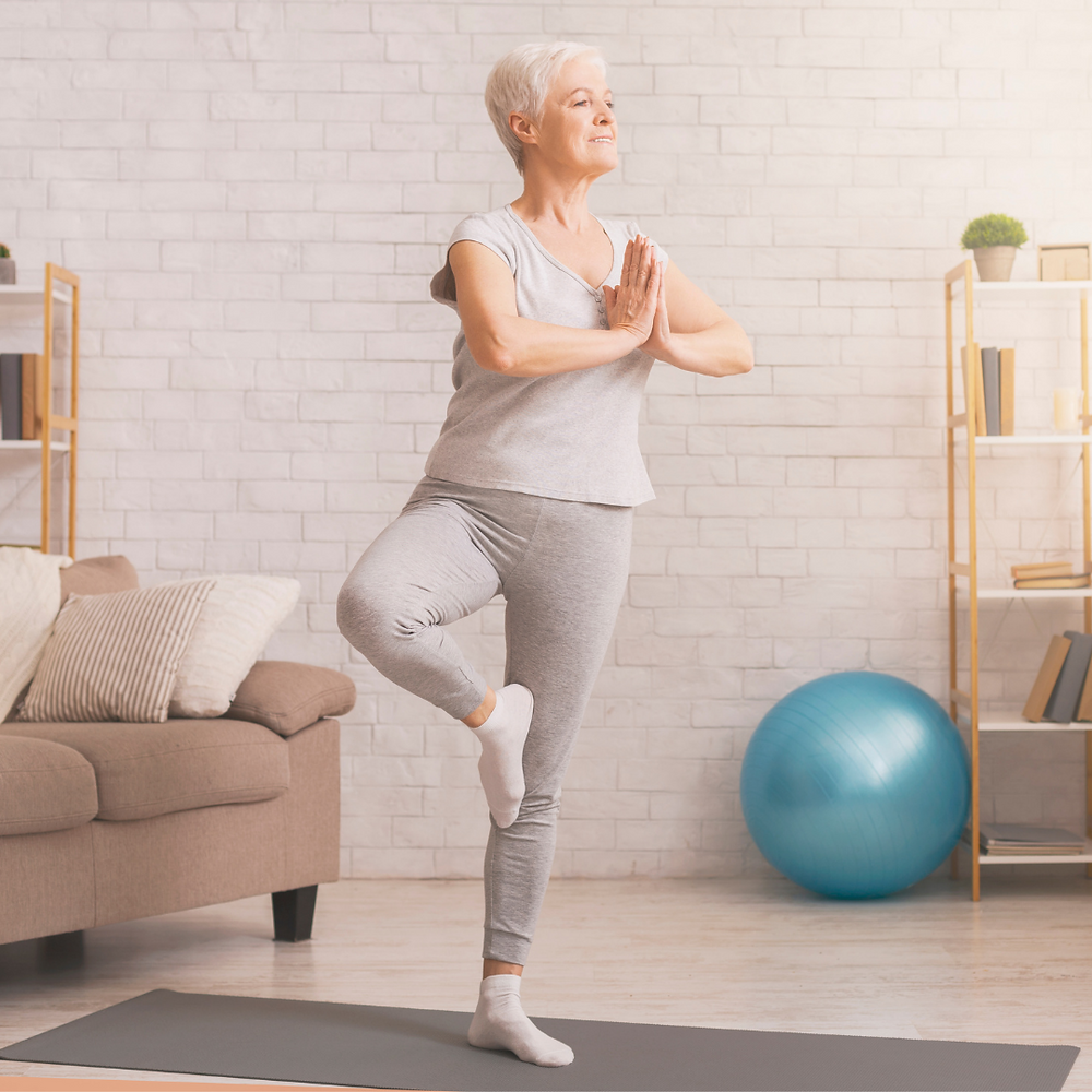 older lady doing a tree pose on a grey yoga mat at home in her living room