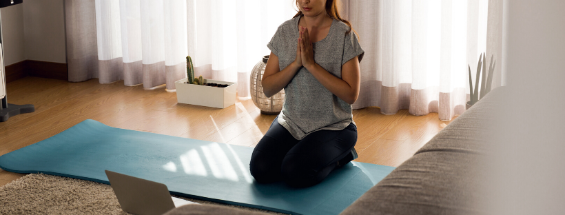 Women wearing yoga clothes doing a kneeling meditative yoga pose on a blue mat in her bedroom doing a live online yoga class from her laptop computer