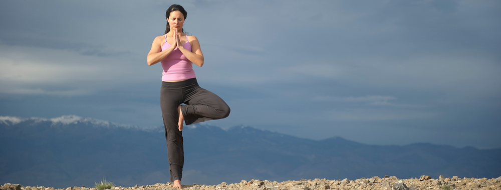 lady doing yoga, ekpadasana or tree pose, working on her balance as a beginner yogi