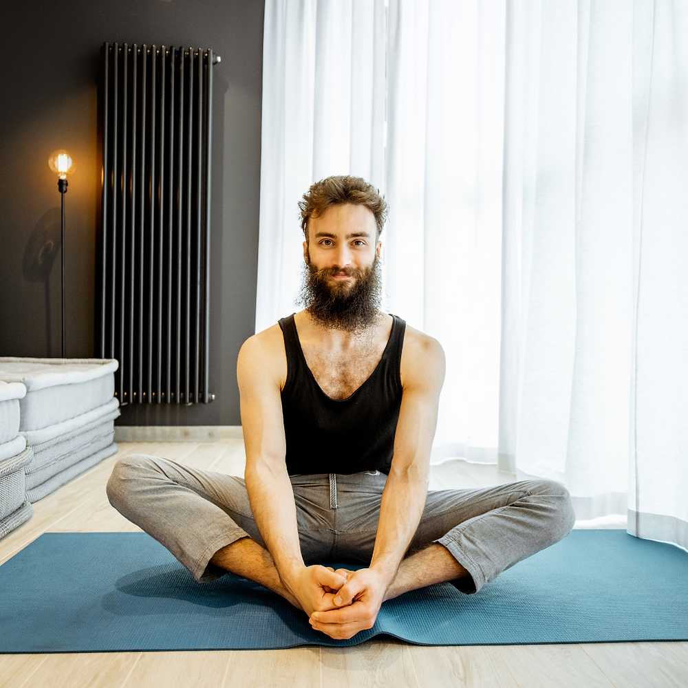 bearded man wearing a black vest doing butterfly pose or cobblers pose on a blue yoga mat in his living room