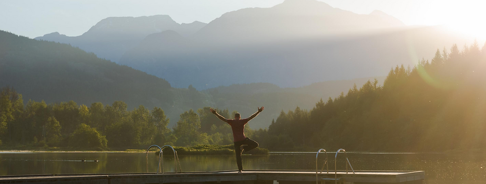 Man doing a tree pose my a lake in front of some mountains
