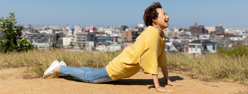 Older Chinese lady doing a cobra yoga pose outdoors with a big smile on her face