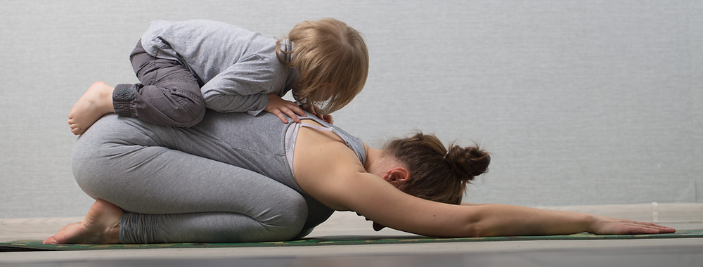 lady doing yoga in child's pose on the floor to help with her period pain and her little boy resting on her back