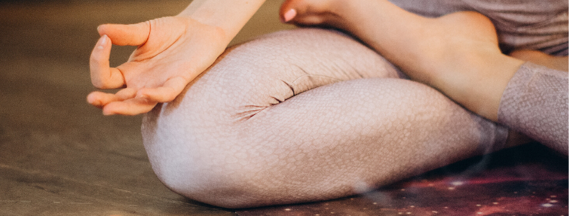 Female yoga student's leg and hand in a seated meditative yoga position on a purple yoga mat at home