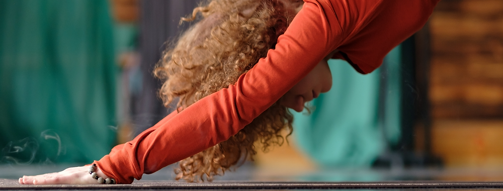 Curly haired lady doing a downward dog yoga pose in her living room