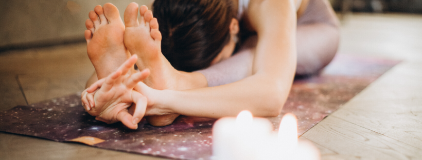 Female yoga student in a forward fold on a purple mat with two candles