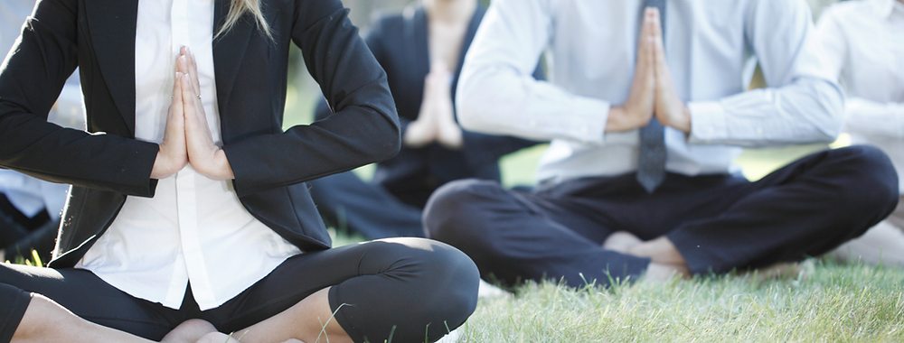 employees practicing yoga for mental health in the workplace. sitting in suits, shirts and ties, with their shoes and socks off and practicing meditation.