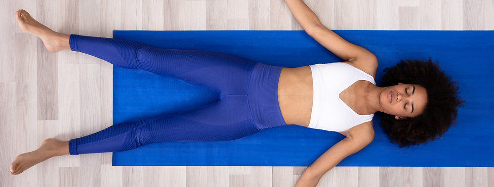 African lady wearing blue yoga leggings lying on a blue yoga mat practicing live online yoga at home for Blue Monday to fight feelings of depression and anxiety.