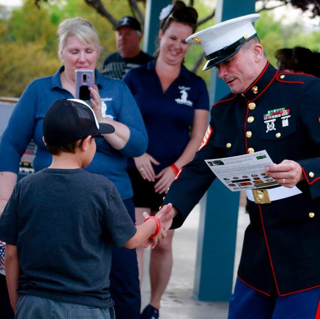 Saluting marine giving incuragment to a school kid